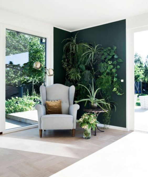 green corner with floating plants, wooden floor, white wall, grey chair, wooden round side table