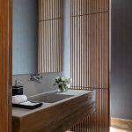 Grid Wooden Partition In The Bathroom, Wooden Floor, Wooden Floating Cabinet, White Top And Sink, Mirror, Grey Wall