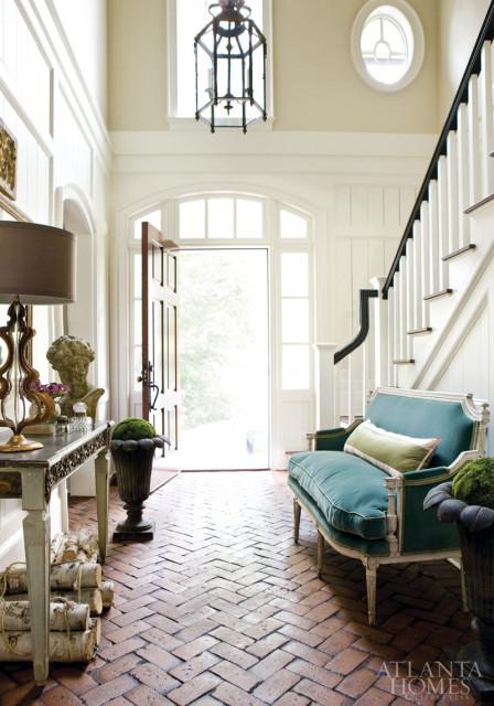 herringbone brick floor on the entrance, console table, table lamp, pendant, green sofa