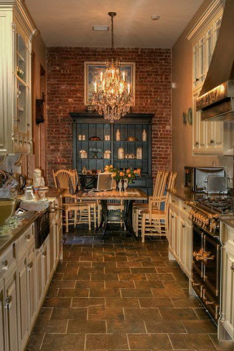 kitchen, brown floor, open brick accent wall, plain wall, white bottom cabinet, chandelier, dining set,