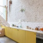 Kitchen, Grey Floor, Pale Yellow Cabinet, White Wall, White Subway Backsplash, Hanging Plants