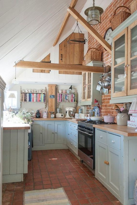 kitchen, red floor, brick accent wall, white wall, green bottom cabinet, sloping ceiling, wooden beam, green upper cabinet