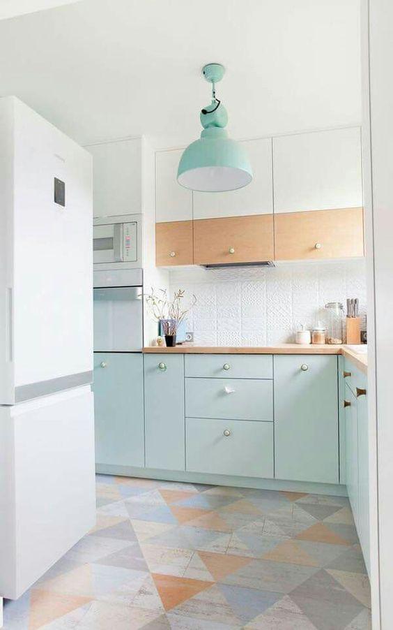 kitchen, soft colored patterned floor, white wall, white backsplash, white fridge, white wooden upper cabinet, soft green bottom cabinet, green pendant