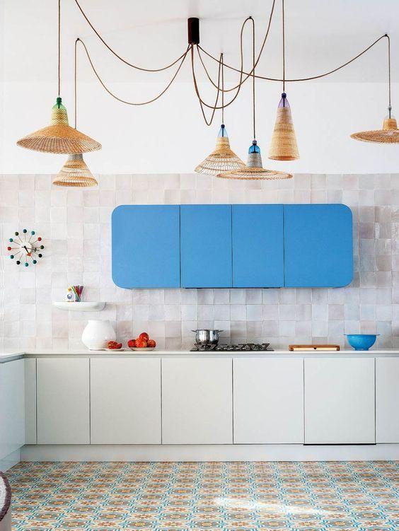 kitchen, white bottom cabinet, patterned floor, white wall, white backsplash tiles, blue upper cabinet, pendants