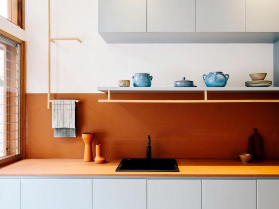 kitchen with white bottom cabinet, orange kitchen top, orange backsplash wall, white wall, white floating shelves, white upper cabinet