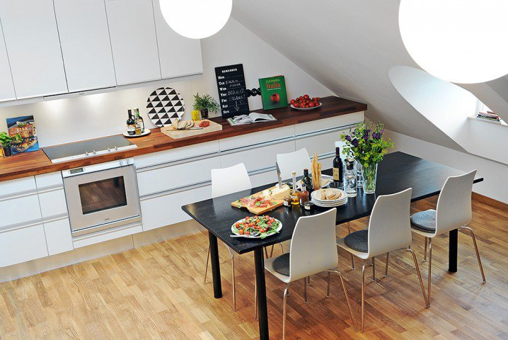 kitchen with white cabinet, wooden top, white upper cabinet, white wall, black dining table, white modern chairs, wooden floor, white pendant