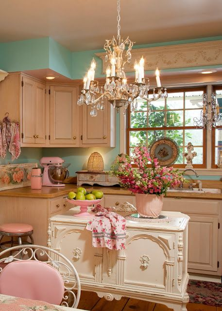 kitchen with wooden floor, turquoise wall, white cabinet, wooden top, white cabinet with details, pink chair