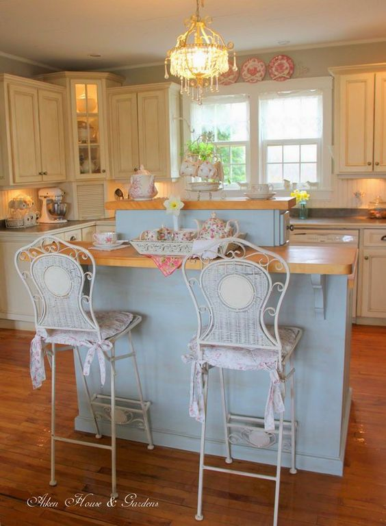 kitchen with wooden floor, white wooden cabinet, blue island with white detailed stool, chandelier