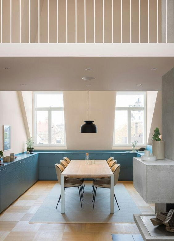 kitchen, wooden floor, beige wal, tall glass window, blue bottom cabinet, blue rug, wooden dining set