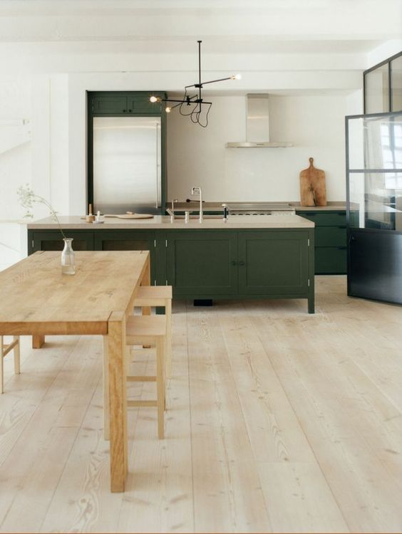 kitchen, wooden floor, white wall, dark moss cabinet and island with light top, pendant, wooden dining set