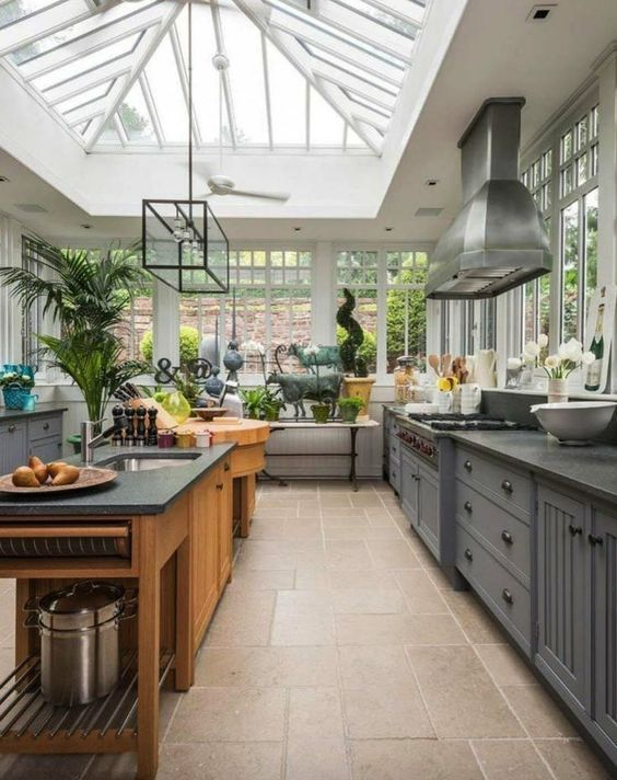 kitchens under glass sloping ceiling, brown tiles floor, window glass, grey kitchen cabinet, wooden island in the middle