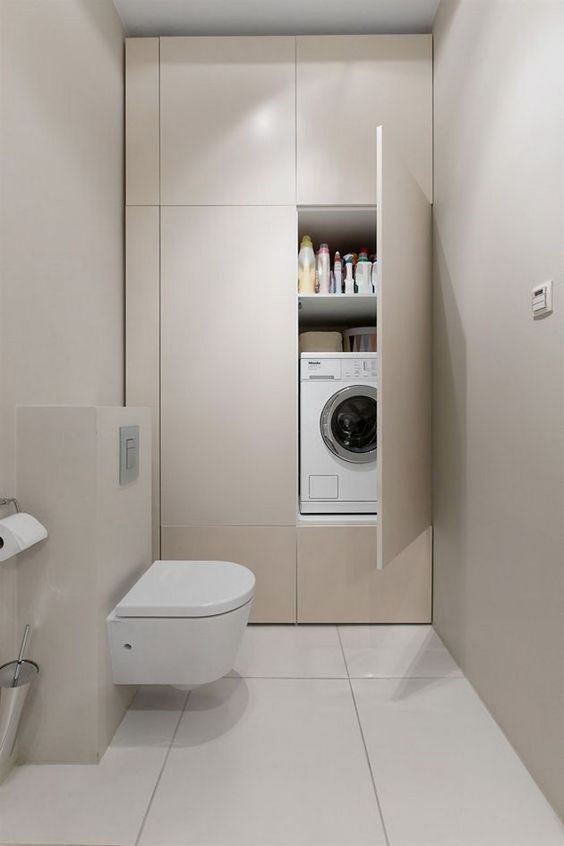 laundry machine inside white bilt in cupboard in the bathroom, white wall, white floor, white floating toilet