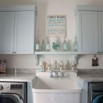 Laundry Room Decorations Blue Cabinets Wall Decor Glass Bottle White Marble Countertop White Apron Sink Faucet Washing Machine Artwork