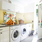 Laundry Room Decorations Yellow Wall White Cabinets White Door Gray Floor Tile Washing Machine Artwork White Drawer Black Countertop