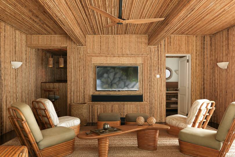 living room, bamboo wall ceiling, wooden floor, bamboo chairs, wooden table, ottoman, wooden ceiling