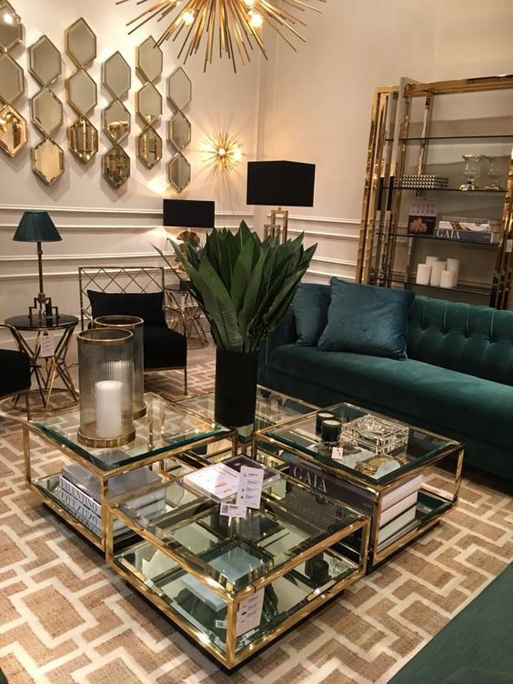 living room, brown patterned rug, brown wall, deep green sofa, glass top coffee table, mirrored wall decor, black floor lamp, black chairs, glass shelves, chandelier