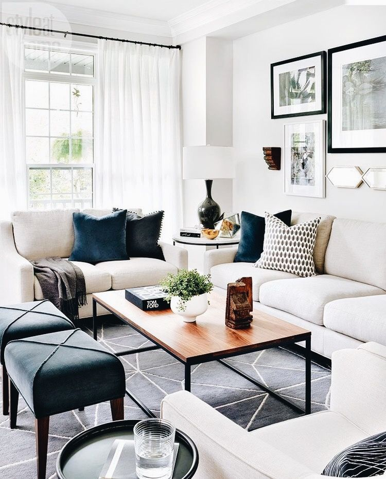 living room, dakr rug with white lines, white wll white sofa, black ottomans, wooden coffee table, white side table, black white table lamp