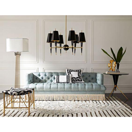 living room, dark wooden floor, white rug, soft blue tufted sofa, white wall, black covered chandelier, black white stool with golden legs, black side table, white floor lamp