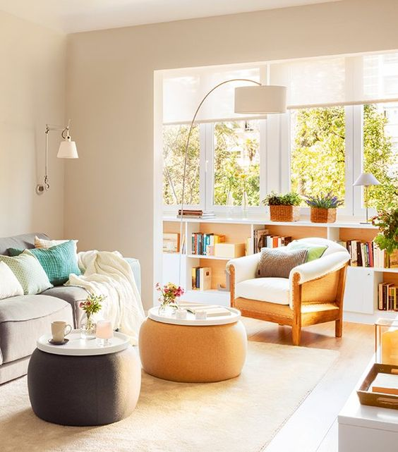 living room, light floor, beige rug, off white wall, white pendant, white floor, low bookshelves, white chair, grey sofa, brown grey round ottoman with white tray