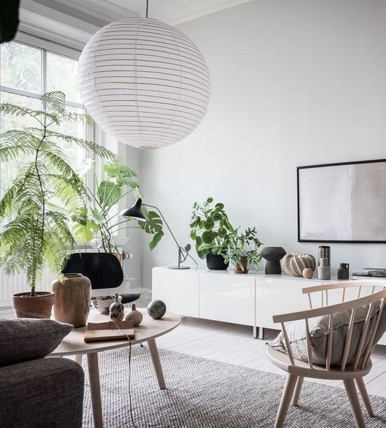 living room, light wooden floor, grey rug, wooden chair, grey sofa, white wall, white cabinet, white pendnat, large glass windows