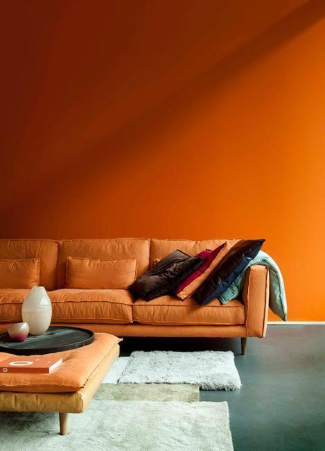 living room, orange wall, orange sofa, orange swuare ottoman, grey floor, white rug