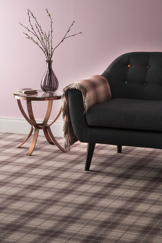 living room, pastel plaid floor, pink wall, black sofa with colorful tufted buttons, copper side table