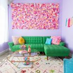 Living Room, Soft Purple Wall, Pink Flower, Brown Marble Floor, Brown Patterned Rug, Green Tufted Sofa, Blue Chair, Glass Coffee Table