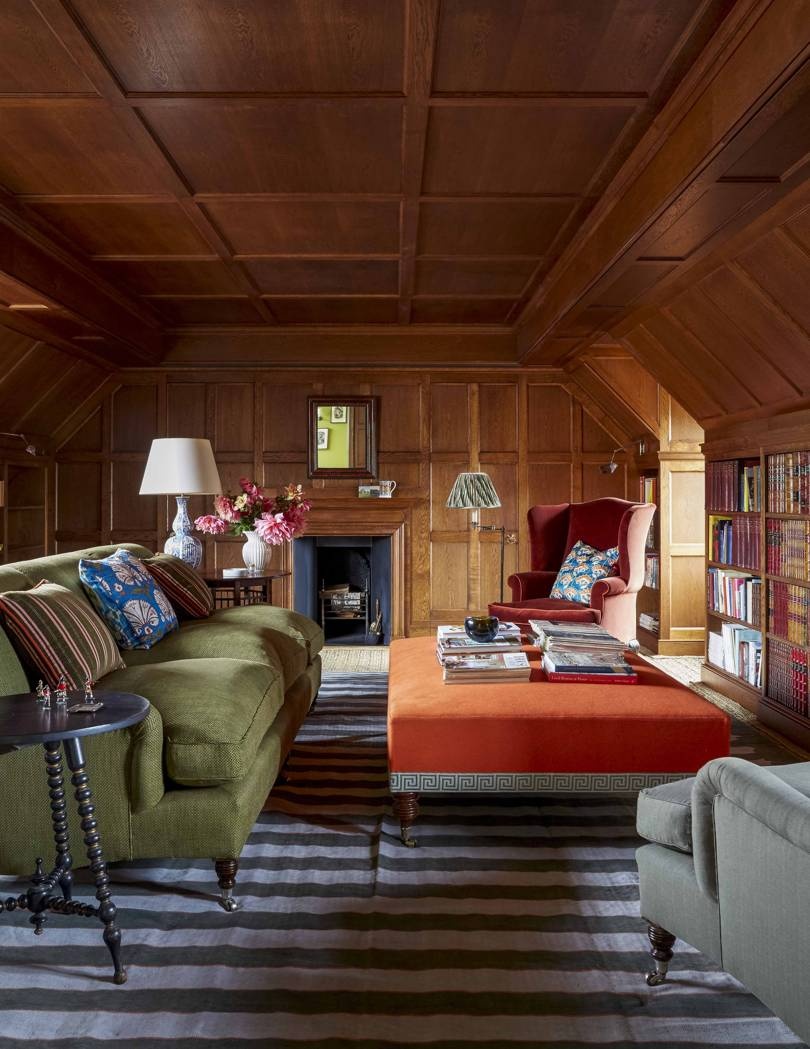 living room, stripe grey rug, wooden ceiling, wooden wall paneling, green sofa, orange ottoman for pinnaple, grey chair,