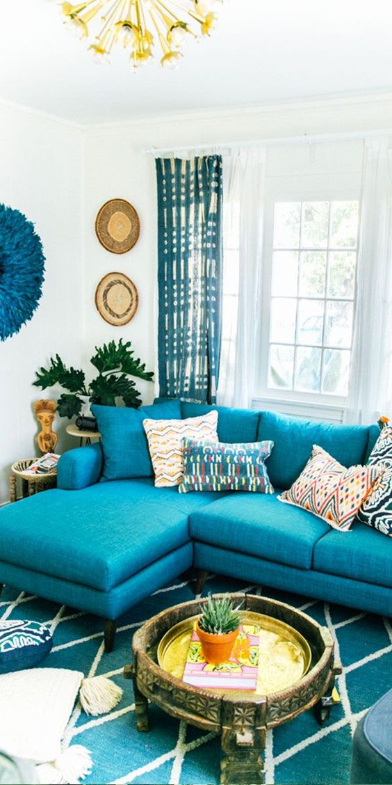 living room, turquoise sofa, blue patterned rug, white wall, golden pendants, low golden tray coffee table