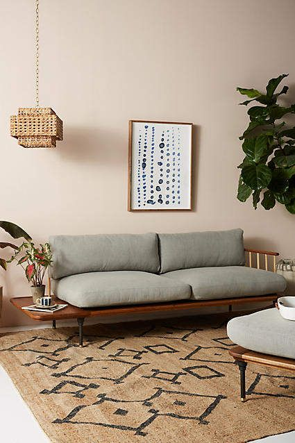 living room, white floor, brown rug, brown wooden bench with shorter cushion in grey, rattan pendant, coffee table with cushion
