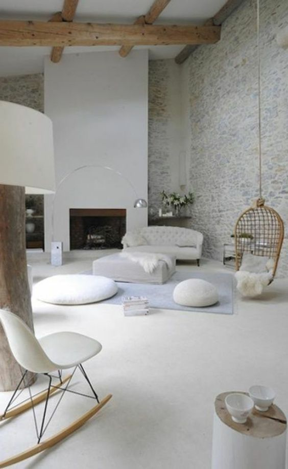 living room, white floor, white sofa, ottoman, and rocking chair, rattan swing, grey wall, wooden beams