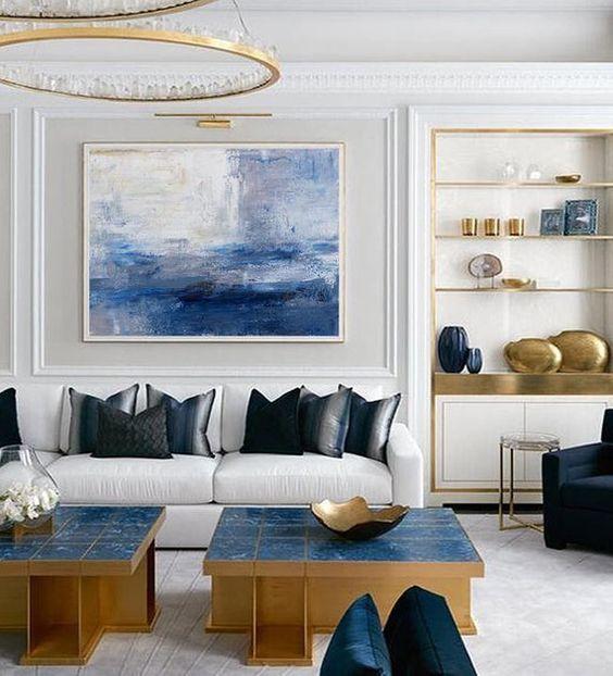 living room, white floor, white wall, white sofa, blue topped coffee table, black chair, white shelves, golden ringchandelier, crystal accent