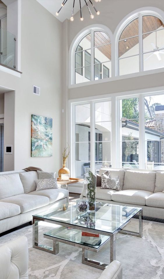 living room, white marble floor, white wall, white sofas, glass topped coffee table with silver support, tray side table, large and tall window