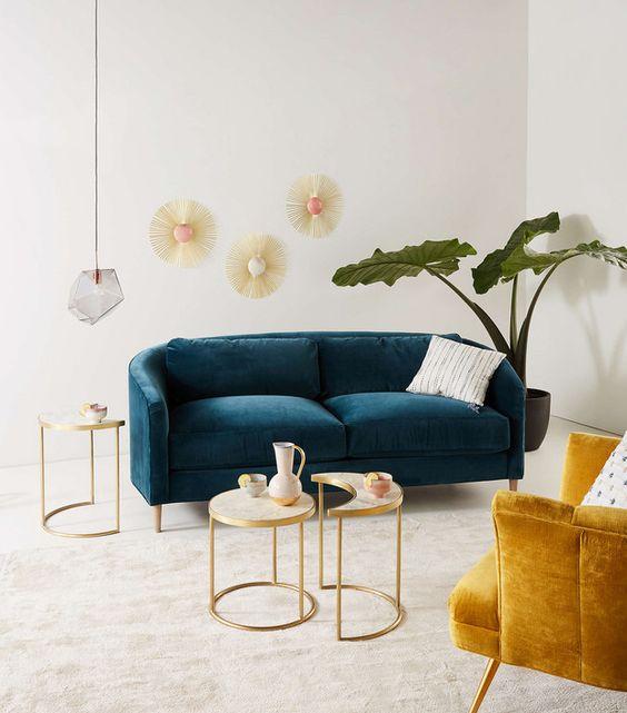 living room, white rug floor, white wall, deep green velvet sofa, yellow velvet chair, white coffee table