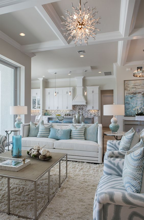 living room, white rug, whtie sofa, blue patterned chair, white ceiling, sun chandelier, coffee table