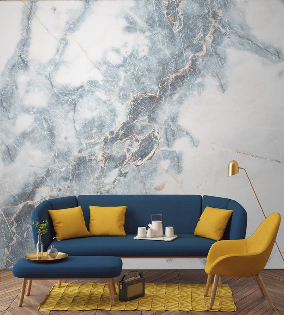 living room, wooden chevron floor, yellow chair, yellow rug, blue sofa, blue long ottoman for coffee table, golden floor lamp, yellow pillows