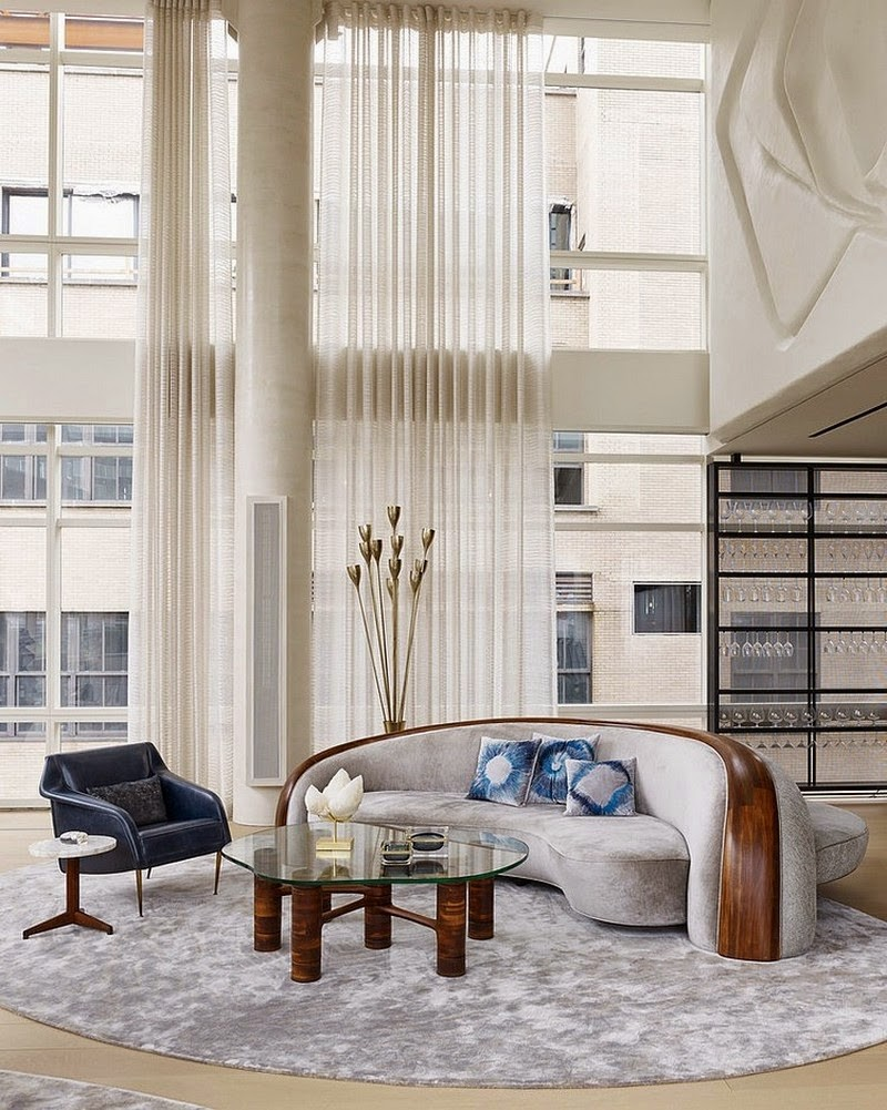 living room, wooden floor, grey round rug, white pillar, white curtain, grey curvy sofa with wooden frame in the middle, glass topped coffee table, black leather chair