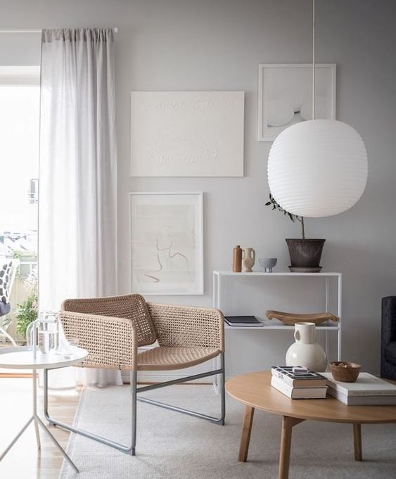 living room, wooden floor, grey rug, wooden coffee table, white wall, white pendant, white curtain, white shelves, black sofa