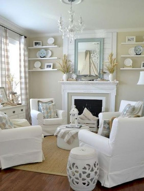 living room, wooden floor, rattan rug, beige wall, white ceiling, white chairs, white ottoman, white fireplace