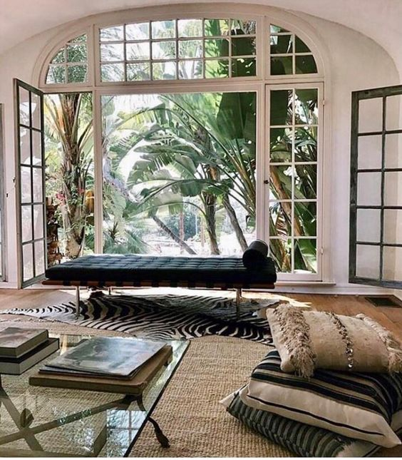 living room, wooden floor, rattan rug, white wall, glass window and door, black bed, glass top coffee table, pillows