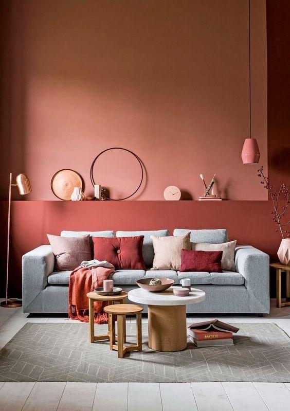 living room, wooden floor, terracotta wall, pink pendant, grey sofa, round coffee tables, grey rug