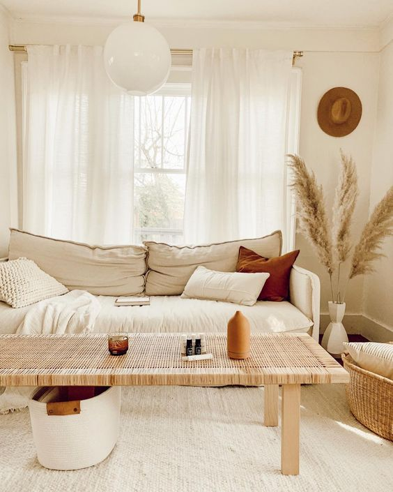 living room, wooden floor, white rug, wooden rattan table, white sofa, rattan basket, white wall, white globe pendant