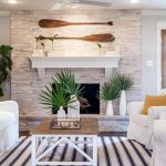Living Room, Wooden Floor, White Stone Accent Wall, White Floating Shelves, Fire Place, White Sofa, Whtie Chairs, Striped Rug, Wooden Coffee Table
