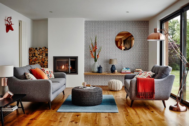 living room, wooden floor, white wall, accent wall, grey chairs, blue rug, woven ottoman, black coffee table, mirror, floating woodeng shelves