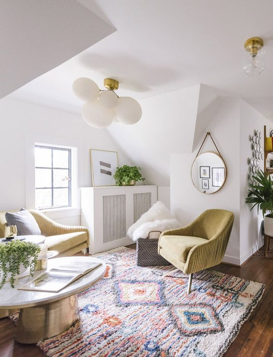 living room, wooden floor, white wall, sloping ceiling, colorful rug, green sofa and chair, silver coffee table, white chandelier