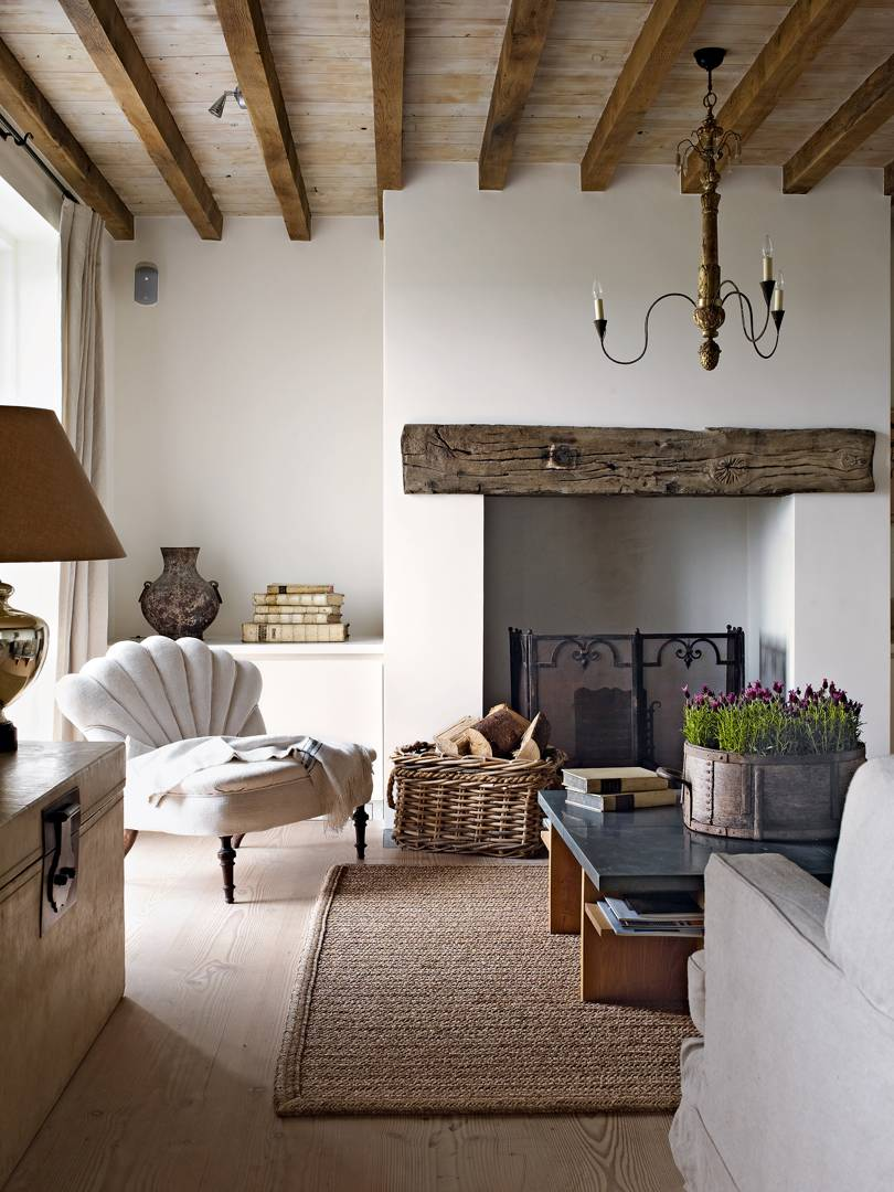 living room, wooden floor, white wall, white wall fireplace, shelves on alcove, wooden chest, wood coffee table with black top, chandelier, white chair