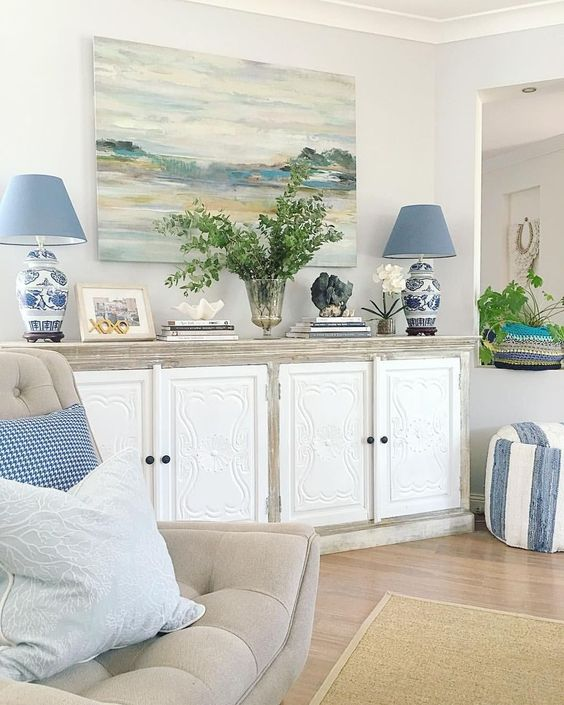 living room, wooden floor, white wall, white wooden cabinet, beige chair, blue table lamp, blue pillows