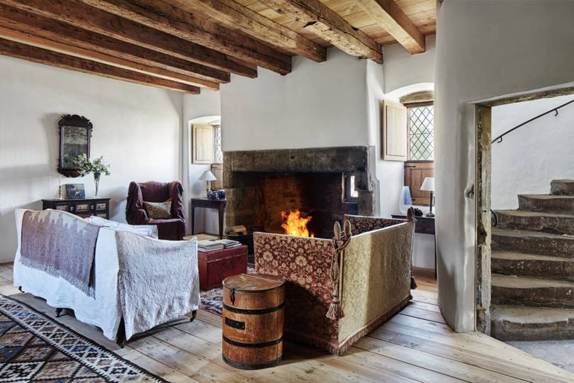 living room, wooden floor, white wall, wooden ceiling with beams, chairs and sofa, chest table, stone fireplace, window