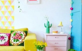 living room, wooden floor, white wall, yellow wall painted decoration, yellow sofa, coffee table, pale pink side cabinet, blue wall partition