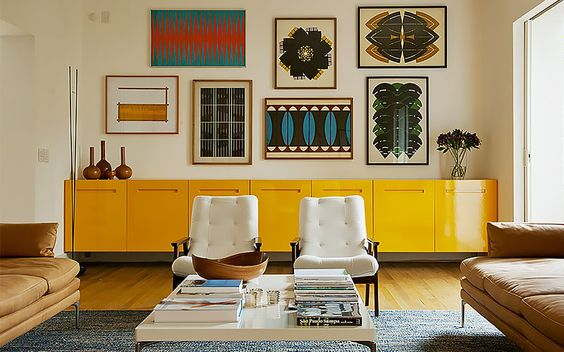 living room, wooden floor, yellow long cabinet, white wall, wall accessories, grey rug, white coffee table, whie chairs, brown sofas